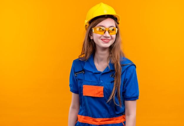 De jonge arbeider van de vrouwenbouwer in eenvormige bouw en veiligheidshelm die opzij glimlachend vrolijk status kijken
