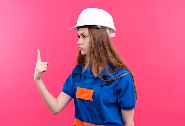 De jonge arbeider van de vrouwenbouwer in eenvormige bouw en veiligheidshelm die opzij kijken die wijsvinger met fronsend gezicht tonen dat zich over roze muur bevindt