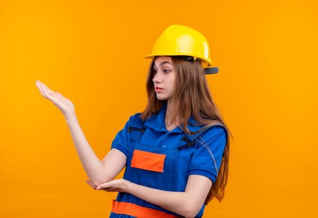 De jonge arbeider van de vrouwenbouwer in eenvormige bouw en veiligheidshelm die opzij kijken ontevreden opheffend hand die status over oranje muur opstelt
