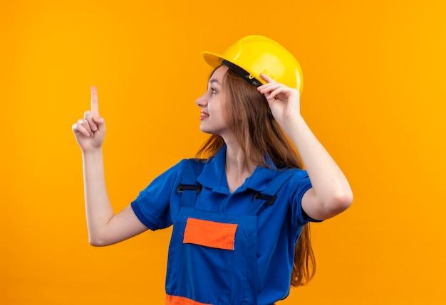 De jonge arbeider van de vrouwenbouwer in eenvormige bouw en veiligheidshelm die opzij met glimlach op gezicht kijken die wijsvinger status tonen