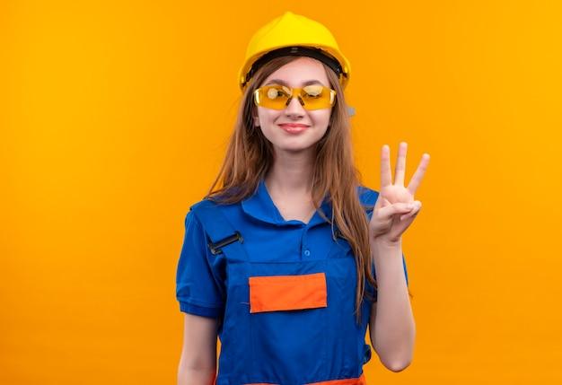 De jonge arbeider van de vrouwenbouwer in eenvormige bouw en veiligheidshelm die tonen en met vingers omhoog wijzen nummer drie die zich over oranje muur bevinden