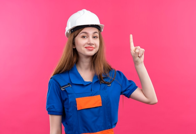 De jonge arbeider van de vrouwenbouwer in eenvormige bouw en veiligheidshelm die vinger benadrukken met geweldig idee glimlachend staande over roze muur