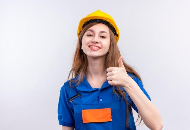 De jonge arbeider van de vrouwenbouwer in eenvormige bouw en veiligheidshelm die vrolijk tonen duimen die omhoog zich over witte muur bevinden
