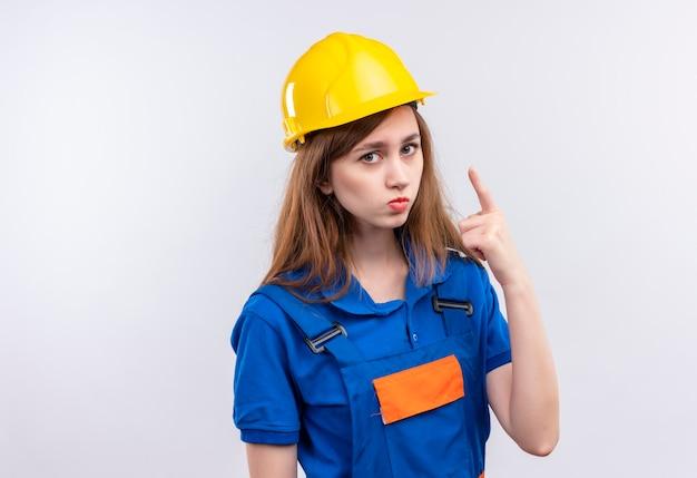 De jonge arbeider van de vrouwenbouwer in eenvormige bouw en veiligheidshelm die wijsvingerwaarschuwing tonen voor gevaar met fronsend gezicht dat zich over witte muur bevindt