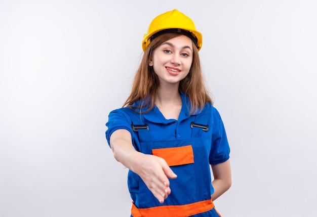 De jonge arbeider van de vrouwenbouwer in eenvormige bouw en veiligheidshelm die zelfverzekerd groetgebaar maken die hand aanbieden die zich over witte muur bevinden