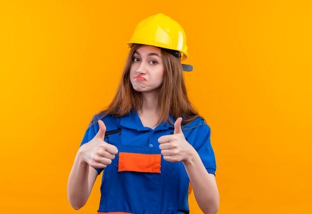 De jonge arbeider van de vrouwenbouwer in eenvormige bouw en veiligheidshelm die zelfverzekerd tonen duimen opdagen met beide handen die zich over oranje muur bevinden
