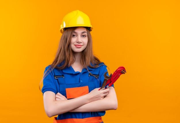 De jonge arbeider van de vrouwenbouwer in eenvormige bouw en veiligheidshelm die zich met gekruiste wapens bevinden die holdingsmoersleutel zich zeker over oranje muur bevinden kijken