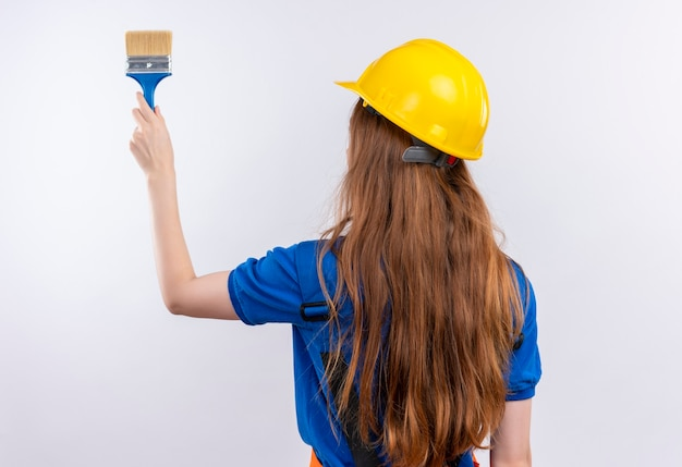 De jonge arbeider van de vrouwenbouwer in eenvormige bouw en veiligheidshelm die zich met haar rug houden verfborstel over witte muur