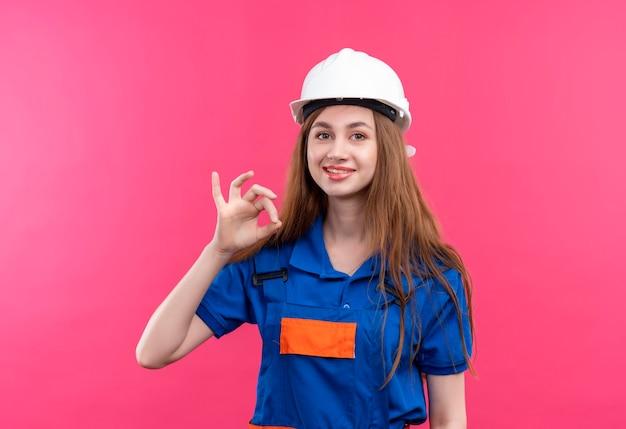De jonge arbeider van de vrouwenbouwer in eenvormige bouw en veiligheidshelm het gelukkige en positieve glimlachen tonend ok teken dat zich over roze muur bevindt