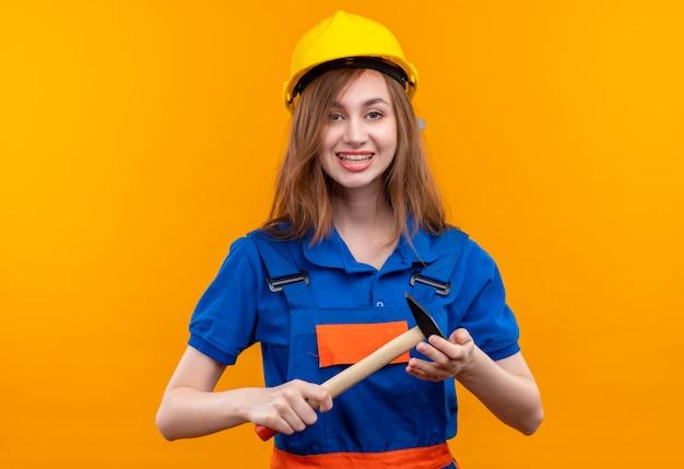 De jonge arbeider van de vrouwenbouwer in eenvormige bouw en veiligheidshelm positieve en gelukkige het glimlachen holdingshamer die zich over oranje muur bevindt