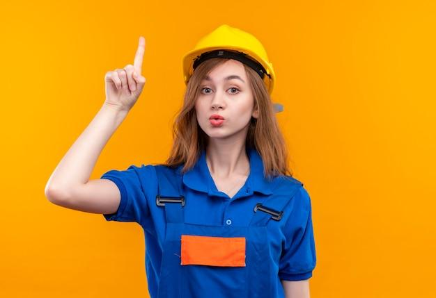 De jonge arbeider van de vrouwenbouwer in eenvormige bouw en veiligheidshelm, wijzende wijsvinger op waarschuwing met ernstig gezicht dat zich over oranje muur bevindt