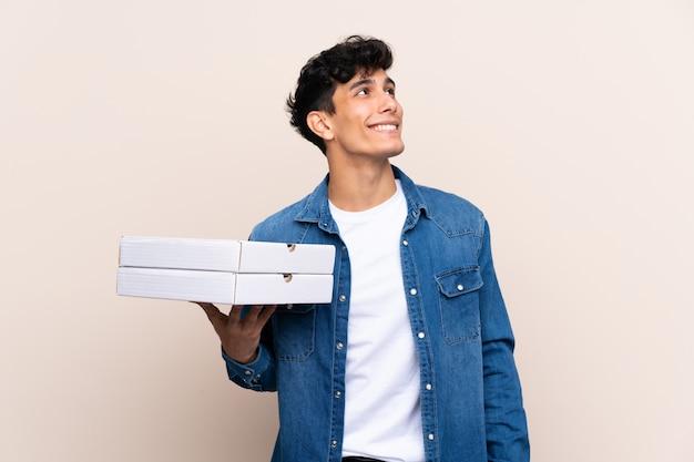 De jonge argentijnse pizza's van de mensenholding over geïsoleerde muur die omhoog terwijl het glimlachen kijken