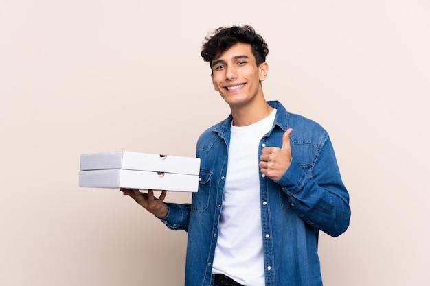 De jonge argentijnse pizza's van de mensenholding over geïsoleerde muur met omhoog duimen omdat iets goeds is gebeurd