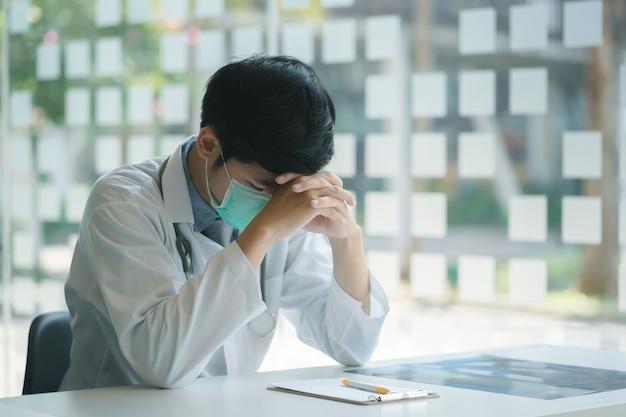 De jonge arts die stethoscoop draagt beklemtoonde met overgewerkte migrainehoofdpijn en spanning.