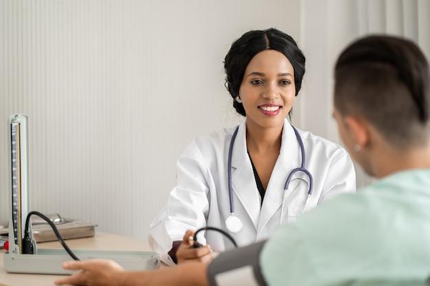De jonge arts meet de bloeddruk voor de patiënt.