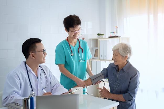 De jonge arts raadpleegt hogere patiënt die op artsenkantoor zit