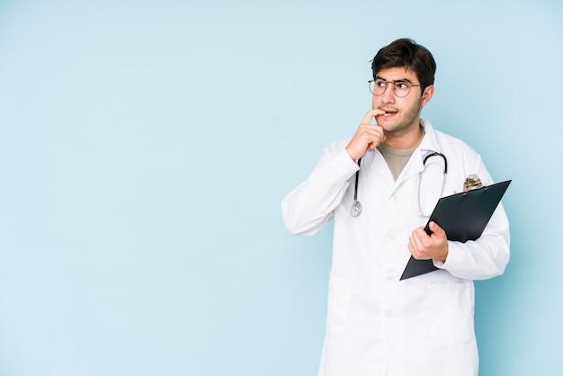 De jonge artsenmens op blauwe muur ontspande het denken over iets bekijkend een lege ruimte.