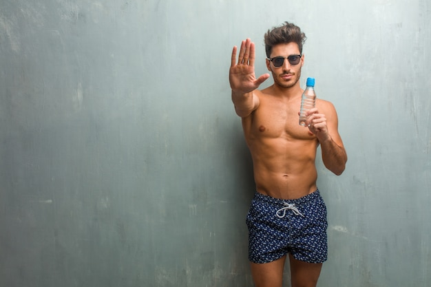 De jonge atletische mens die een zwempak dragen tegen een ernstige en bepaalde grungemuur, hand vooraan zet, houdt gebaar tegen, ontkent concept