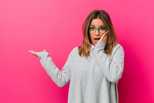 De jonge authentieke charismatische echte mensenvrouw tegen een muur houdt exemplaarruimte op een palm, houdt wang overhandigen. verbaasd en blij.