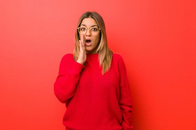 De jonge authentieke charismatische vrouw tegen een muur zegt een geheim heet remmend nieuws en kijkt opzij