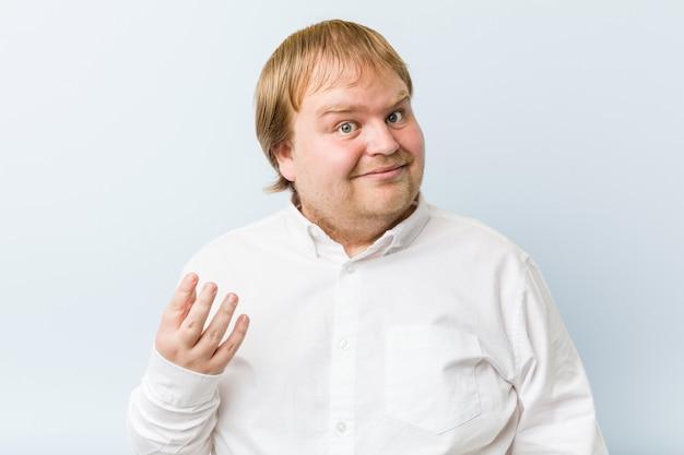 De jonge authentieke roodharige dikke mens die met vinger op u richt alsof het uitnodigen dichter komt.