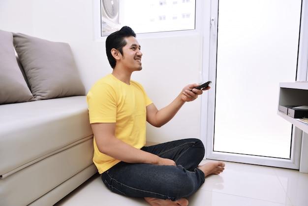 De jonge aziatische afstandsbediening die van de mensenholding op tv let terwijl het zitten