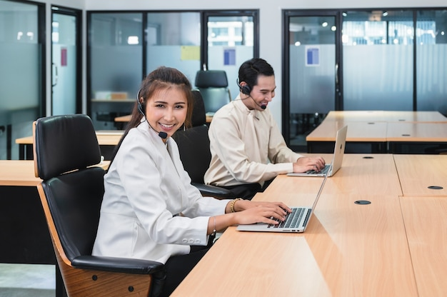 De jonge aziatische agent van de exploitantvrouw met hoofdtelefoons werkende klantenservice in call centre
