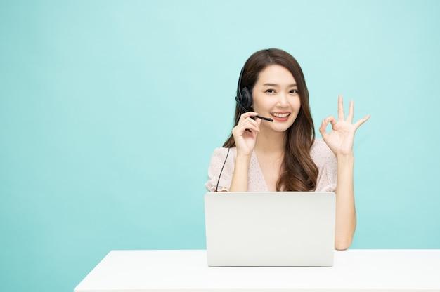 De jonge aziatische agent van de vrouwenvriendelijke exploitant met hoofdtelefoons en het tonen van ok teken dat aan lichtgroene achtergrond werkt