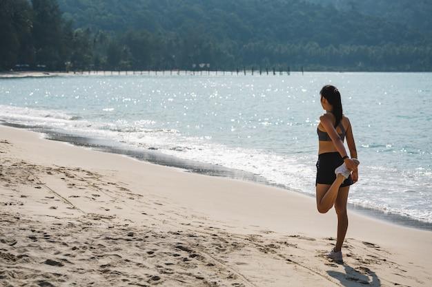 De jonge aziatische agentvrouw ontspant en rekt zich uit op het strand in thailand, sport en gezond vakantieconcept