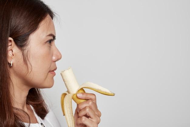 De jonge aziatische banaan van de vrouwenholding