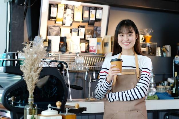 De jonge aziatische barista holding neemt koffiekop met het glimlachen gezicht bij koffie tegenachtergrond