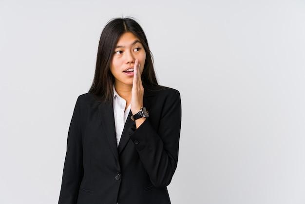 De jonge aziatische bedrijfsvrouw zegt een geheim heet remmend nieuws en kijkt opzij
