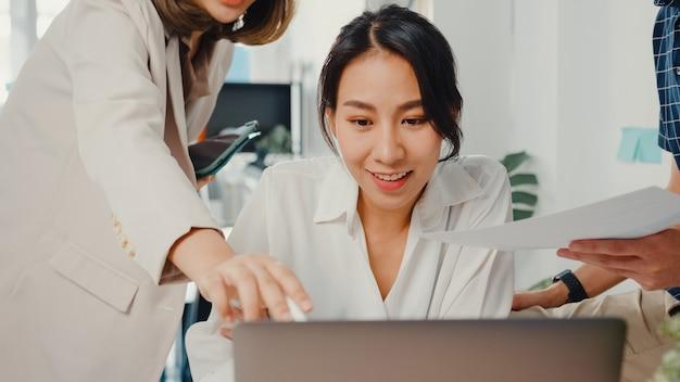 De jonge aziatische creatieve zakenman en de bespreking van de onderneemsterhoofdmanager leggen projectrapport op laptop uit