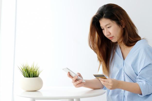 De jonge aziatische creditcard van de vrouwenholding en het gebruiken van slimme telefoon voor online het winkelen