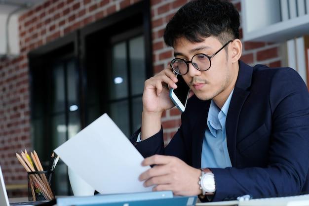 De jonge aziatische documenten die van de zakenmanlezing telefoon spreken op kantoor, bedrijfsmededeling en technologieconcept