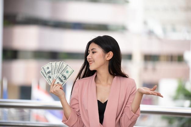De jonge aziatische dollars van de het kostuumholding van de vrouwenslijtage tegen vage zeer van de stadsachtergrond happ