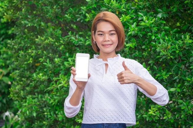 De jonge aziatische glimlachvrouw toont duim met smartphone op groene bladeren.