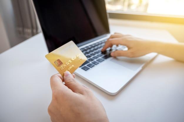 De jonge aziatische hand die van de consumentvrouw een creditcard houdt