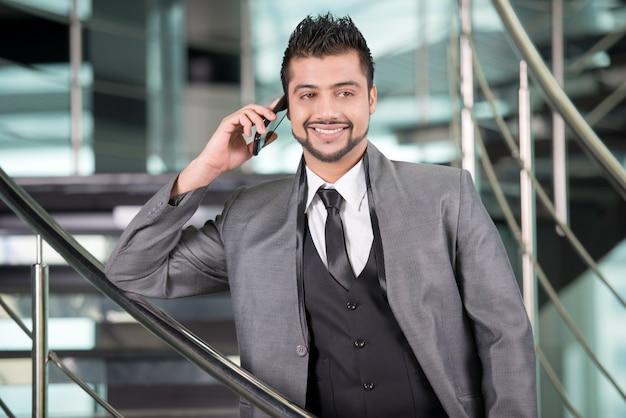 De jonge aziatische indische zakenman spreekt op de telefoon.