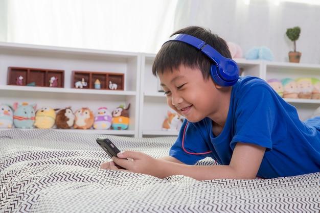 De jonge aziatische jongen in blauwe hoofdtelefoons glimlacht en luistert thuis aan muziek op het bed