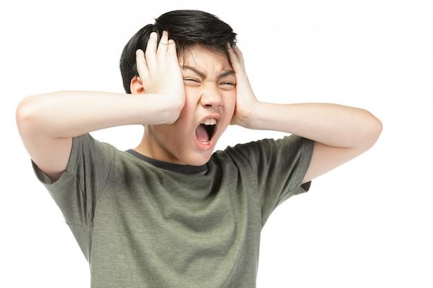 De jonge aziatische jongen over witte achtergrond, is verstoord; heb een slecht humeur emotioneel.