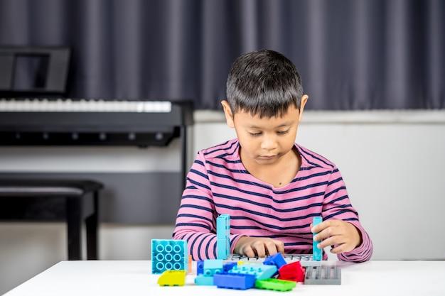 De jonge aziatische jongen speelt lego in de ruimte