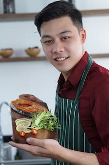 De jonge aziatische kerel is gelukkig met zijn zaken is lapje vleeswinkel