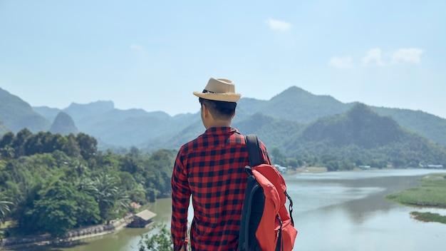 De jonge aziatische man kijkt uit over de bergen en rivieren