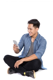 De jonge aziatische mens bekijkt de gsm terwijl het zitten op de vloer