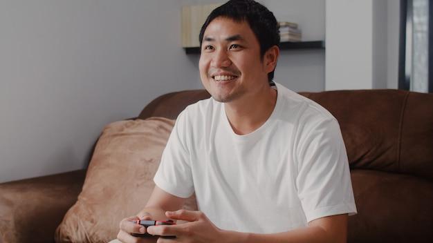 De jonge aziatische mens die bedieningshendel het spelen videospelletjes in televisie in woonkamer gebruiken, mannetje die het gelukkige voelen voelen ontspant tijd thuis liggend op bank. mannen spelen ontspannen thuis.