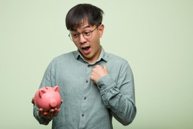 De jonge aziatische mens die een verrast spaarvarken houdt, voelt succesvol en bloeiend
