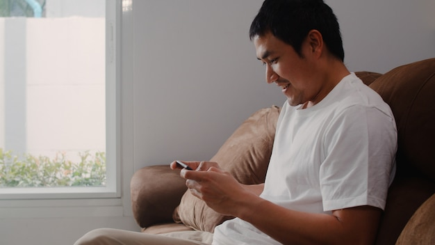 De jonge aziatische mens die mobiele telefoon het spelen videospelletjes in televisie in woonkamer gebruiken, mannetje die het gelukkige voelen voelen ontspant tijd thuis liggend op bank. mannen spelen ontspannen thuis.
