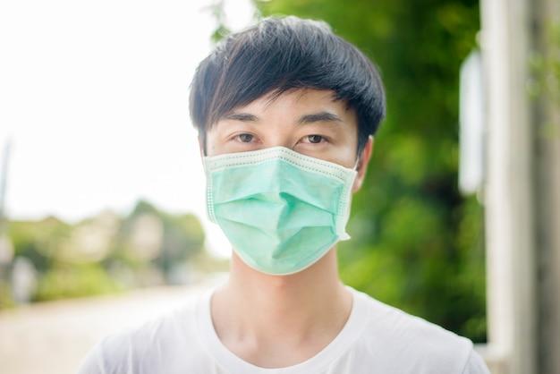 De jonge aziatische mens draagt gezichtsmasker in stad openlucht