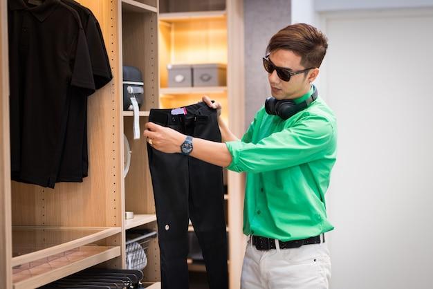 De jonge aziatische mens kleedde zich in toevallige stijl en draagt oogglazen en oortelefoon die broek kiezen